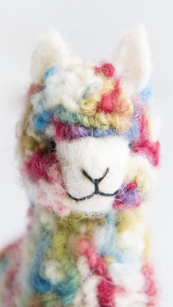 A white background features an adorable multicolored wooly alpaca toy face looking at you along with a June 2020 calendar