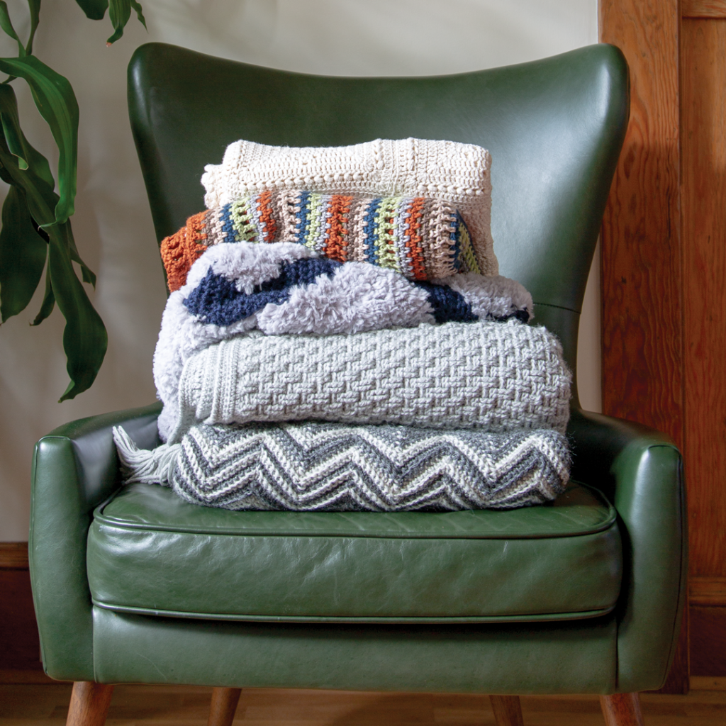 A stack of folded crocheted blankets on a stylish green chair
