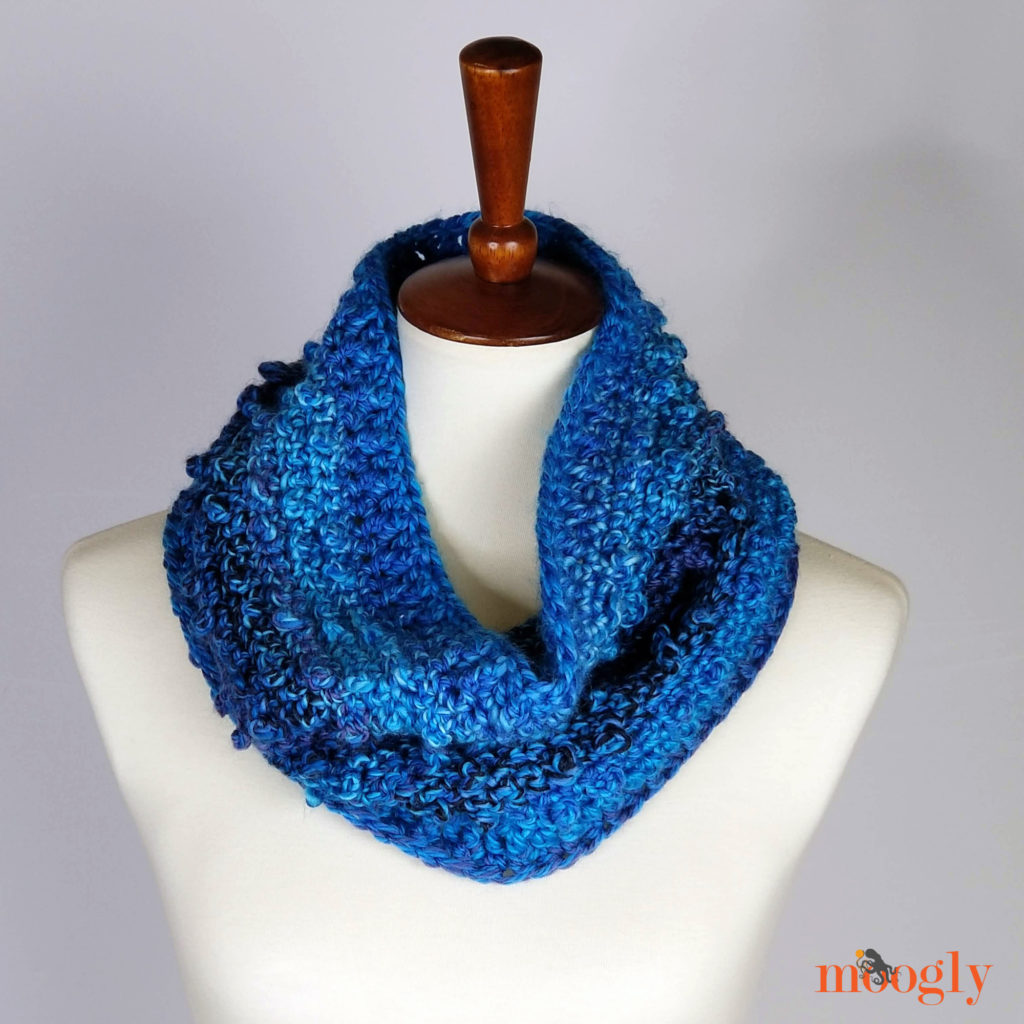Picot Trip Cowl pattern by Moogly. A blue crocheted cowl on a dress form.