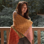 A model wears the Holiday Sweets Shawl: part of the 12 Weeks of Gifting free patterns from Crochet.com