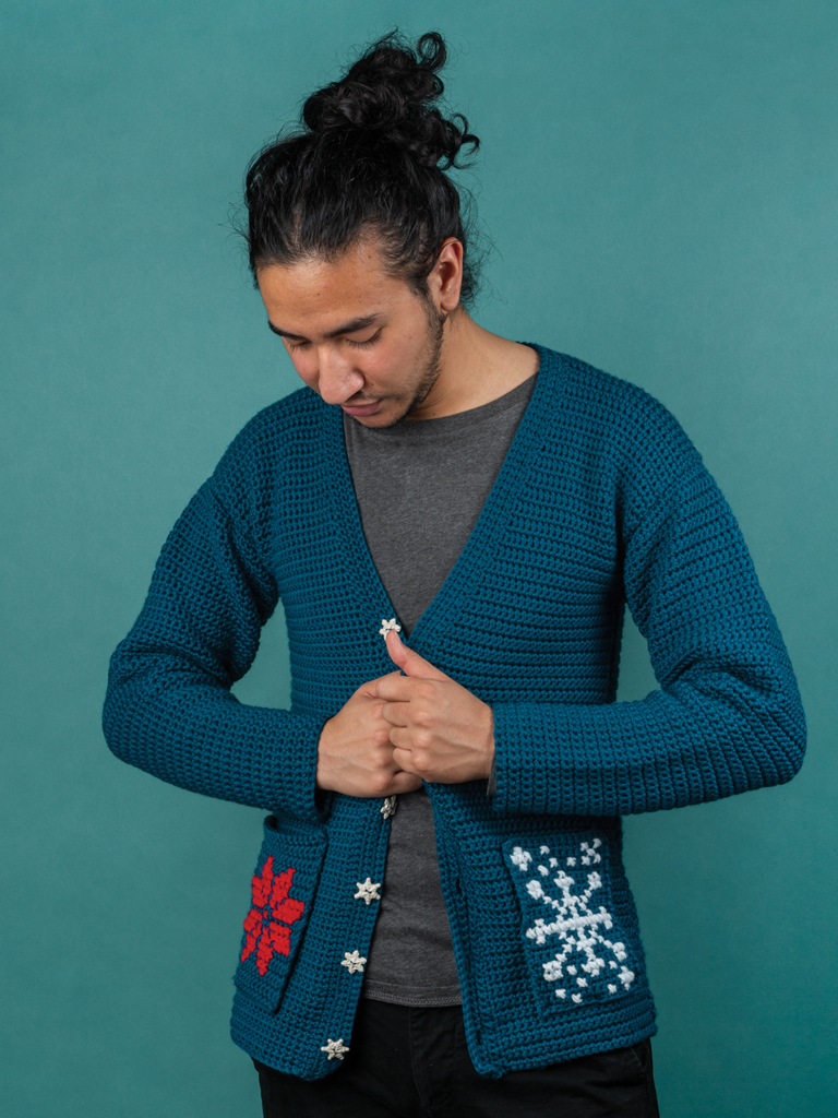 A model wears the Revelry crochet cardigan, a free holiday crochet pattern from crochet.com. A not-ugly sweater for the holidays.