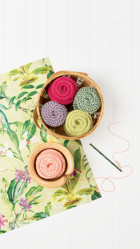 A top-down view of a white background with a floral pattern paper on it, with a yarn bowl filled with colorful cotton yarn.